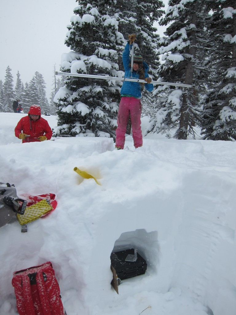 Evaluating snow properties in the mountains after a heavy winter storm.